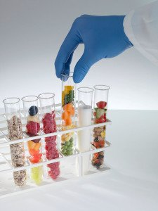 Balanced diet. Scientist selecting a test tube containing vegetables from six, which together represent the components of a healthy diet. The other test tubes contain (from left to right): cereals, fruit, meat, milk and salad. Carbohydrates should make up the largest part of the diet, followed by fresh fruit and vegetables, and proteins. Fats and sugars should make up the smallest part of the diet.